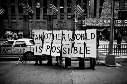 activists holding a sign saying 'another world is possible'